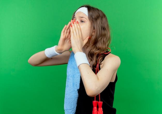 Giovane ragazza di forma fisica in abiti sportivi neri con fascia e asciugamano sulla spalla che grida o chiama qualcuno con le mani vicino alla bocca in piedi sopra la parete verde Foto Gratuite