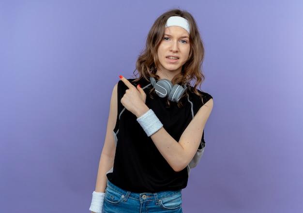 Giovane ragazza di forma fisica in abiti sportivi neri con fascia con espressione scettica che punta indietro in piedi sopra la parete blu Foto Gratuite