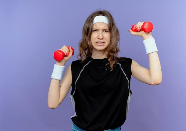 Giovane ragazza di forma fisica in abiti sportivi neri con fascia che lavora con manubri cercando confuso in piedi sopra la parete blu Foto Gratuite