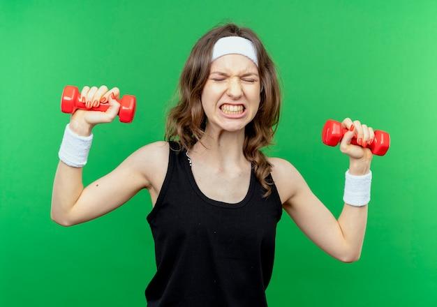 Giovane ragazza di forma fisica in abiti sportivi neri con fascia che risolve con i manubri cercando tesa sul verde Foto Gratuite