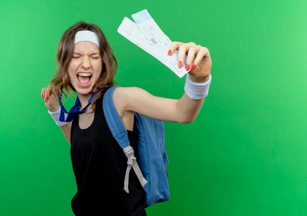녹색 벽 위에 서 행복하고 흥분된 항공 티켓을 보여주는 머리띠와 배낭 검은 운동복에 젊은 피트니스 소녀 무료 사진