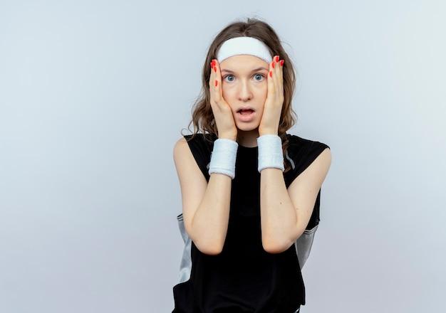 그녀의 얼굴을 잡고 머리띠와 검은 운동복에 젊은 피트니스 소녀 흰색 벽 위에 서 충격을 받고 무료 사진