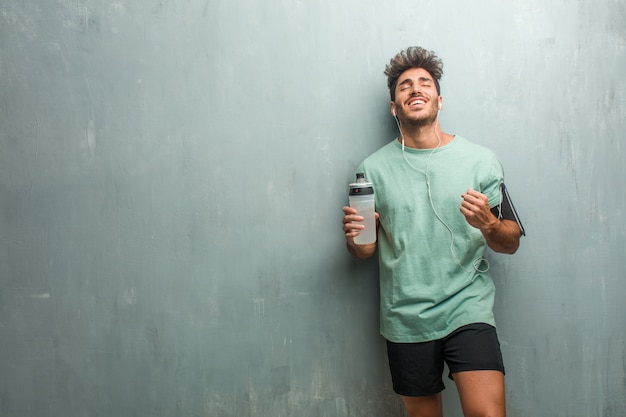 Young fitness man against a grunge wall very happy and excited, raising arms Premium Photo