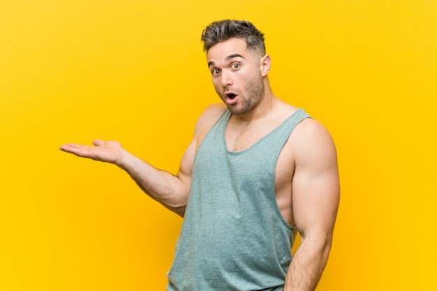 Young fitness man against a yellow impressed holding copy space on palm. Premium Photo