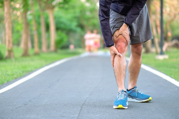 Young fitness man holding his sports leg injury Premium Photo