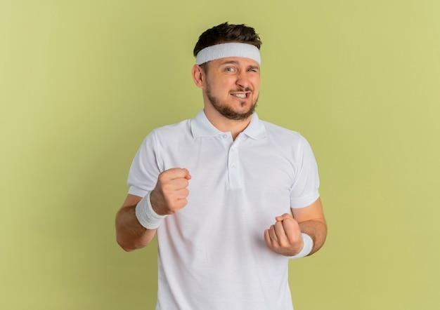 ヘッドバンドと白いシャツを着た若いフィットネス男、オリーブの壁の上に立って混乱しているように見える拳を握り締める 無料写真