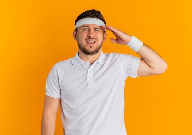 オレンジ色の壁の上に立っている頭の上の手と混同して正面を向いているヘッドバンドと白いシャツを着た若いフィットネス男 無料写真
