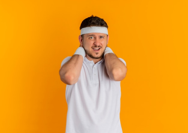オレンジ色の壁の上に立って不快感を感じて正面を向いているヘッドバンドと白いシャツの若いフィットネス男 無料写真