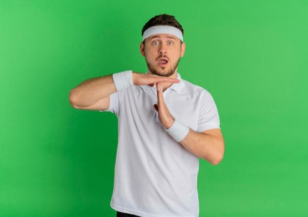 緑の壁の上に立って驚いた手でタイムアウトジェスチャーを作るヘッドバンドと白いシャツを着た若いフィットネス男 無料写真