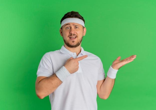 Молодой фитнес-мужчина в белой рубашке с повязкой на голову, указывая пальцем в сторону, представляя руку его руки, стоящую над зеленой стеной Бесплатные Фотографии