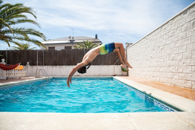 Young fitness man jumping into the water in the pool one day of summer vacation Premium Photo