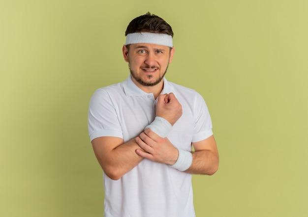 Giovane uomo di forma fisica in camicia bianca con fascia guardando in avanti, toccando il polso che ha dolore in piedi sopra il muro di oliva Foto Gratuite