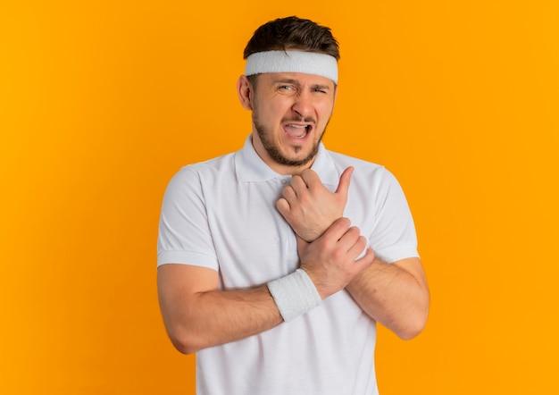 Giovane uomo di forma fisica in camicia bianca con la fascia che guarda al polso commovente anteriore che ha dolore che si leva in piedi sopra la parete arancione Foto Gratuite