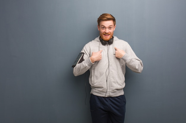 Young fitness redhead man surprised, feels successful and prosperous Premium Photo