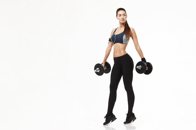 Женщина молодого фитнеса sporty в наушниках тренируя держащ гантели на белизне. Бесплатные Фотографии