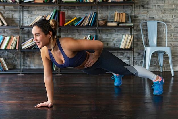 Молодая женщина фитнес делает отжимания тренировки на одной руке на этаже дома Premium Фотографии