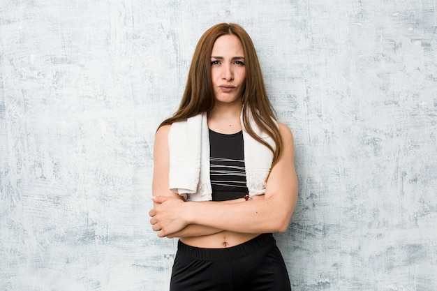 Young fitness woman frowning face in displeasure, keeps arms folded. Premium Photo