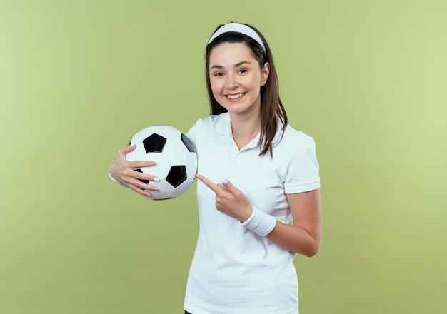 Молодая фитнес-женщина в повязке на голову держит футбольный мяч, указывая пальцем на него, весело улыбаясь, стоя над светлой стеной Бесплатные Фотографии