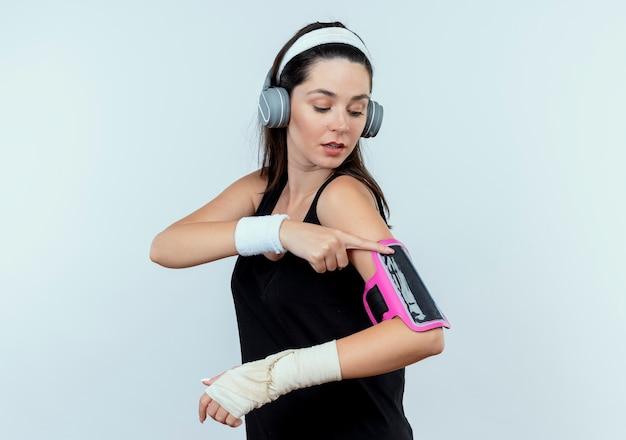 白い壁の上に立って自信を持って見える彼女のスマートフォンの腕章に触れるヘッドフォンでヘッドバンドの若いフィットネス女性 無料写真