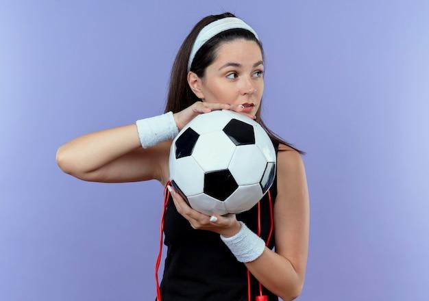 青い壁の上に立っている自信を持って表情で脇を見てサッカーボールを保持している首の周りの縄跳びとヘッドバンドの若いフィットネス女性 無料写真