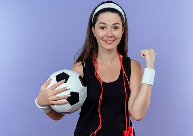 青い壁の上に幸せで前向きに立って幸せで前向きな拳を握りしめながらサッカーボールを保持している首の周りの縄跳びとヘッドバンドの若いフィットネス女性 無料写真