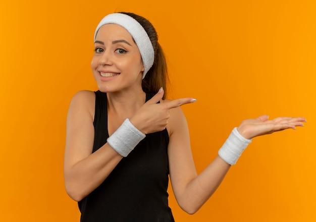 Молодая фитнес-женщина в спортивной одежде с повязкой на голову счастлива и позитивна, указывая руками и пальцем в сторону, стоя над оранжевой стеной Бесплатные Фотографии