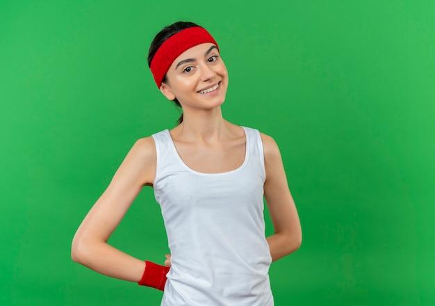 머리띠 행복하고 긍정적 인 녹색 벽 위에 유쾌하게 서있는 스포츠웨어에 젊은 피트 니스 여자 무료 사진
