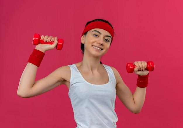 분홍색 벽 위에 서있는 운동을 하 고 자신감을 미소 제기 손에 두 아령을 들고 머리띠와 운동복에 젊은 피트 니스 여자 무료 사진