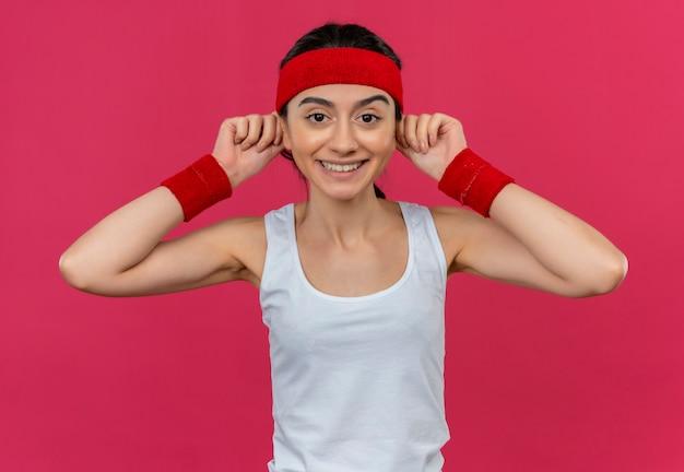 핑크 벽 위에 서있는 얼굴에 큰 미소로 그녀의 귀를 만지고 머리띠와 스포츠웨어에 젊은 피트 니스 여자 무료 사진