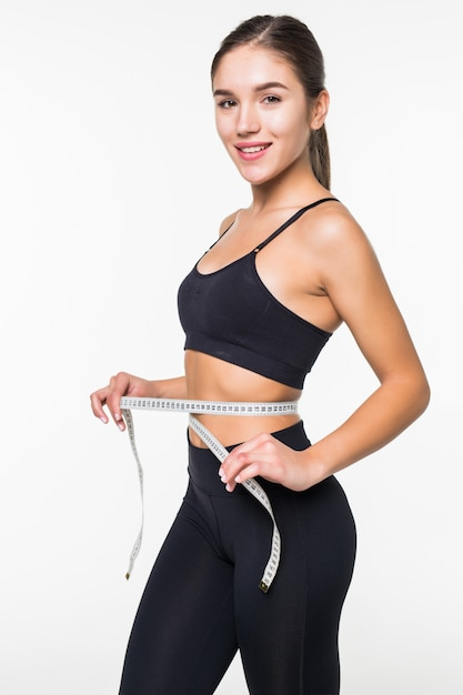 Young fitness woman measure with tape her belly isolated on white wall Free Photo