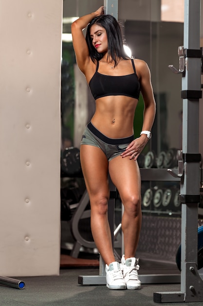 Young fitness woman pulls up in the gym brunette fitness woman in sport wear with perfect muscular body Premium Photo
