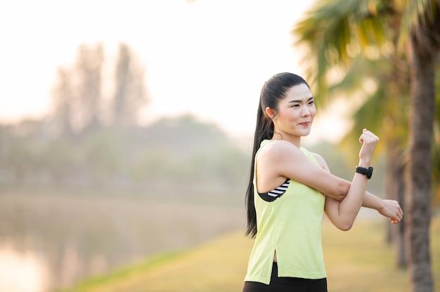 公園で走る前にストレッチする若いフィットネス女性ランナー Premium写真