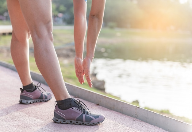 Young fitness woman runner stretching legs before run on city Premium Photo
