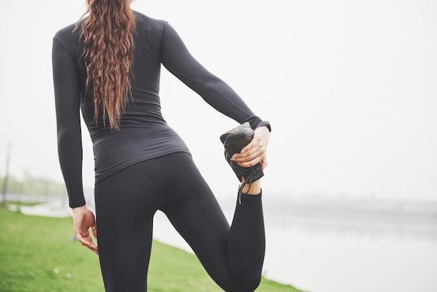 Corridore di giovane donna fitness allungando le gambe prima di correre sul parco Foto Gratuite