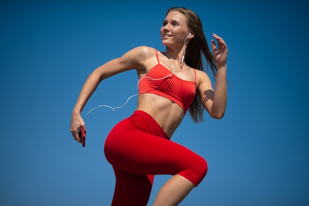 Young fitness woman running on sky backround Premium Photo