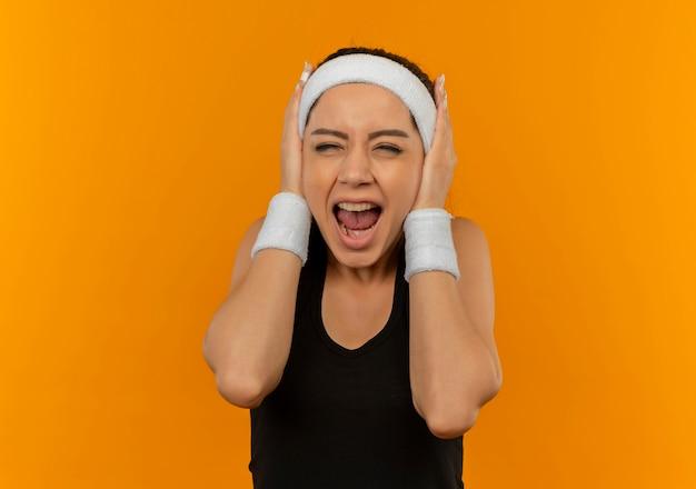 Giovane donna fitness in abiti sportivi con fascia chiudendo le orecchie con le braccia che grida con espressione infastidita in piedi sopra la parete arancione Foto Gratuite