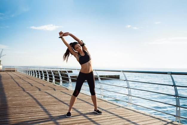 Young fitness woman who makes sport exercises with sea coast behind Free Photo