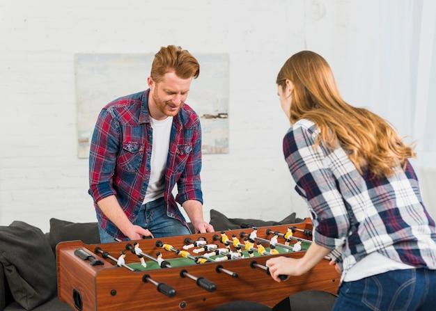 Young focused couple having fun with table soccer game Free Photo