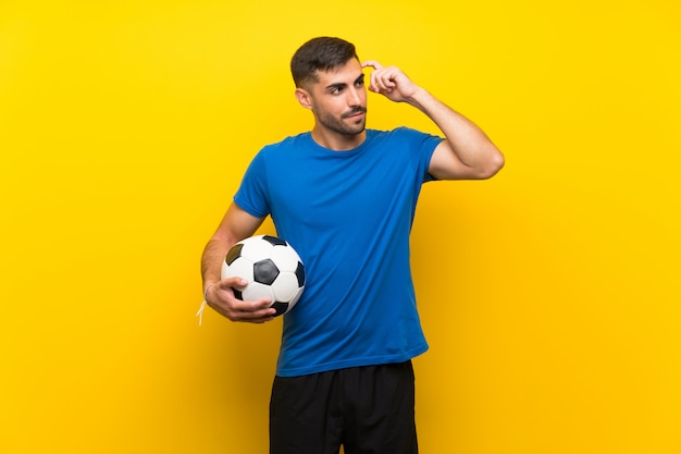 Young football player man having doubts and with confused expression Premium Photo