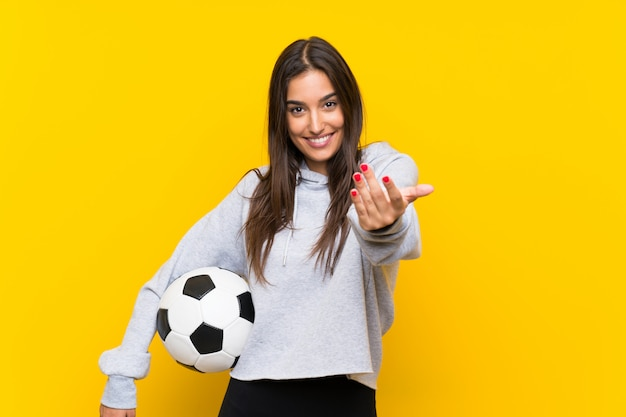 Young football player woman  isolated on yellow  inviting to come with hand. happy that you came Premium Photo