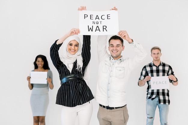 さまざまな国籍の4人の若者の活動家が平和とスローガンを掲げている Premium写真