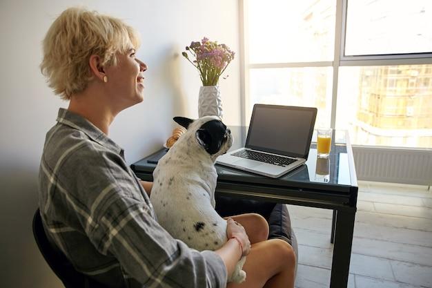 젊은 프리랜서 여성은 휴대용 컴퓨터를 사용하여 집에서 먼 곳에서 일하고 창 옆 테이블에 앉아 그녀의 개를 안고 좋은 분위기에 있습니다. 무료 사진
