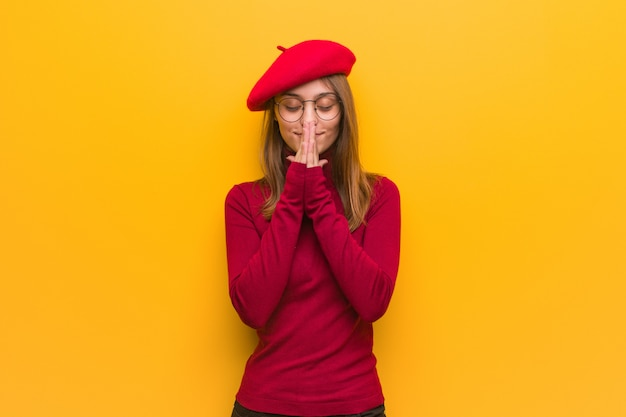 Young french artist woman praying very happy and confident Premium Photo