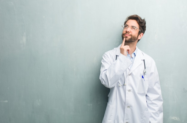 Young friendly doctor man against a grunge wall with a copy space thinking and looking up, confused about an idea, would be trying to find a solution Premium Photo