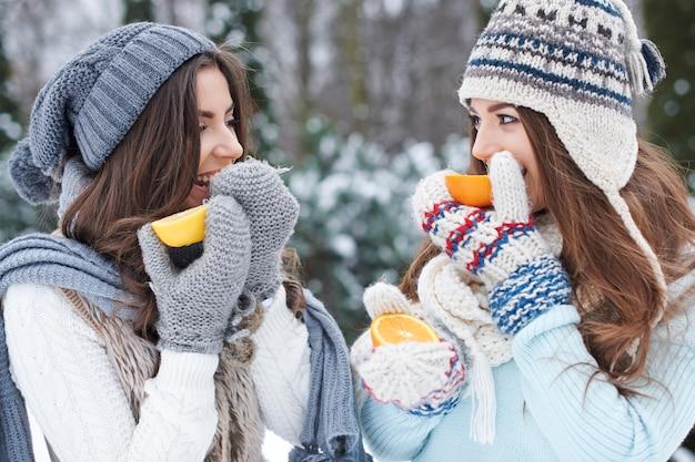 オレンジを食べる若い友達 無料写真