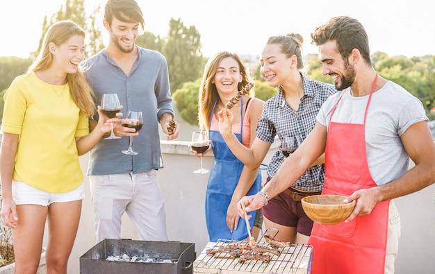 Молодые друзья устраивают вечеринку барбекю на закате в патио дома Premium Фотографии