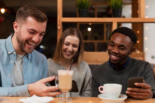 Giovani amici alla ricerca di telefoni Foto Gratuite