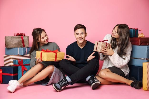 Юные друзья сидят среди рождественских подарочных коробок на розовом Бесплатные Фотографии