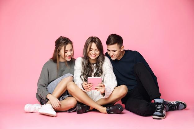 Молодые друзья, улыбаясь, глядя на планшет на розовый Бесплатные Фотографии