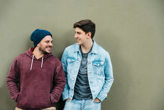 Young friends standing near grey wall Free Photo